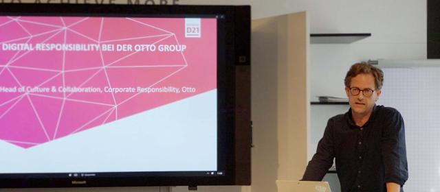 """Stephan Engel trägt neben Bildschirm über """"CDR bei Otto"""" vor"""